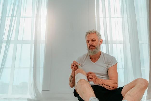 Homem esportivo aplica bandagem protetora antes de iniciar o esporte