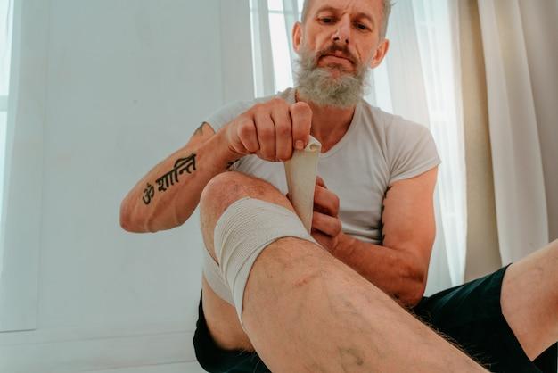 Homem esportivo aplica bandagem protetora para esporte