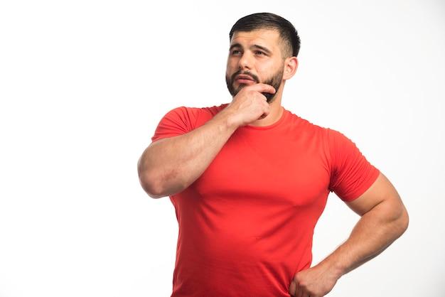 Homem esportivo de camisa vermelha demonstrando os músculos do braço e parece confiante