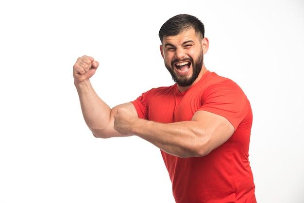 Homem esportivo de camisa vermelha, demonstrando os músculos do braço.