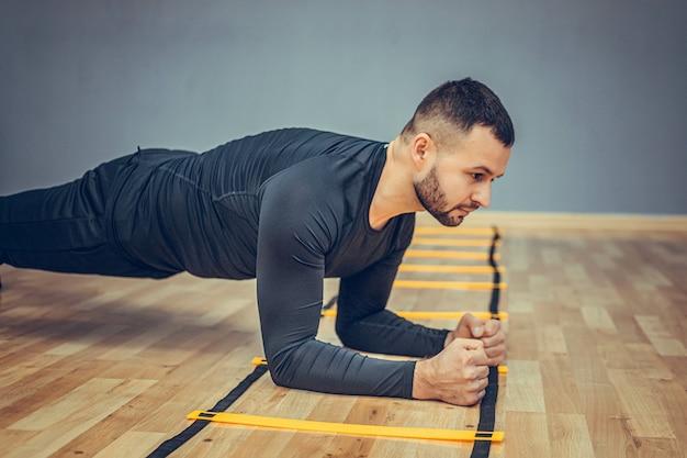 Homem esportivo e atlético treinando fitness fazendo exercícios de prancha na academia