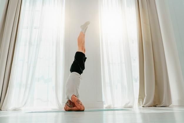 Homem esportivo fazendo exercícios de ioga em casa