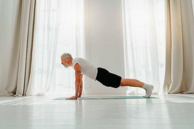 Homem esportivo fazendo exercícios relaxantes de ioga em casa