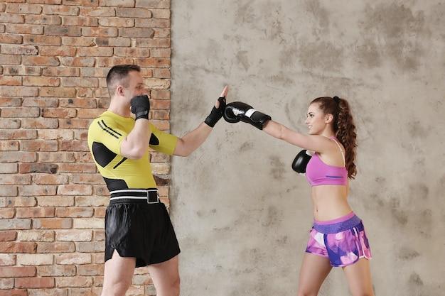 Homem esportivo mostrando técnicas de boxe para a namorada