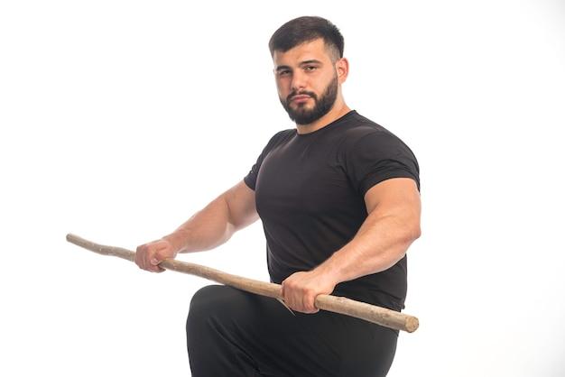 Homem esportivo segurando uma vara de kung fu de madeira nos joelhos.