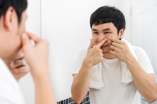 Homem espremendo uma espinha no espelho do banheiro