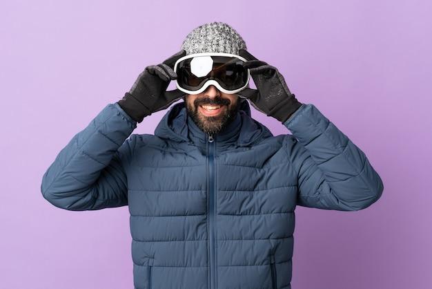 Homem esquiador com óculos de snowboard na parede roxa isolada
