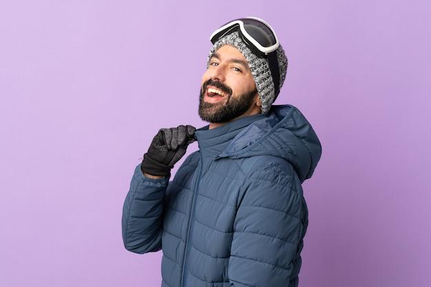 Homem esquiador com óculos de snowboard sobre fundo roxo isolado