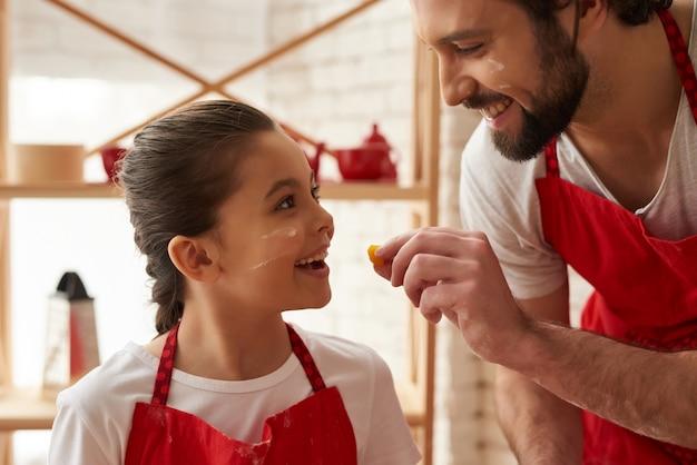 Homem está alimentando filha pequena com pimenta amarela.