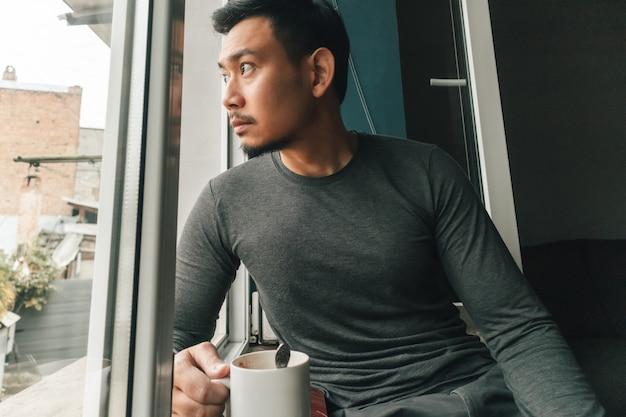 Homem está bebendo café quente e sentindo relaxar pelas janelas.