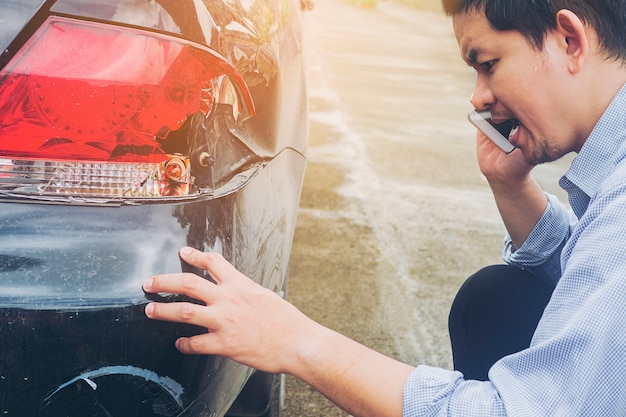 Homem está chamando empresa de seguros para reivindicar seu acidente de carro danificado em acidente de viação
