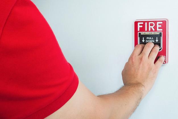 Homem está chegando a mão para empurrar a estação de mão de alarme de incêndio