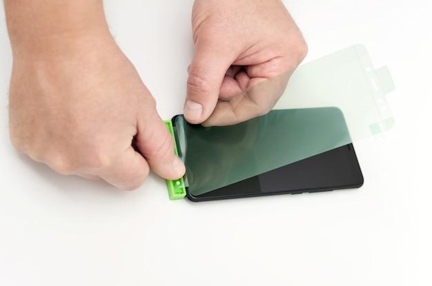 Homem está colando uma película protetora no smartphone.