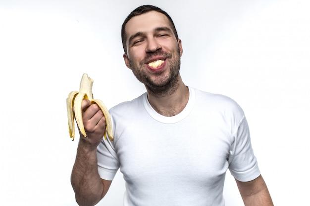 Homem está comendo banana
