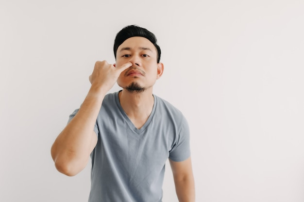 Homem está cutucando o nariz dele, isolado no fundo branco
