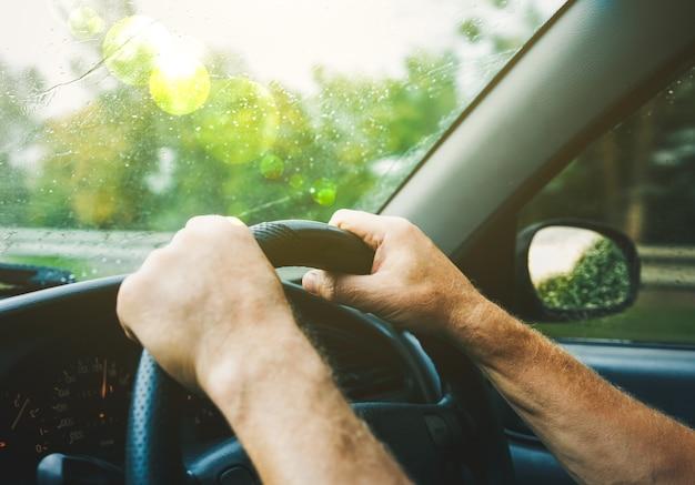 Homem está de mãos dadas no volante do carro. gotas de chuva no pára-brisa. o cara está viajando com o mau tempo. condições perigosas. conceito de estilo de vida.