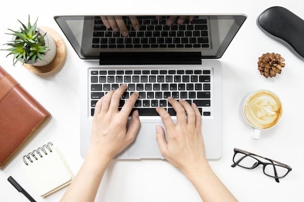 Homem está digitando no teclado do laptop. vista do topo.