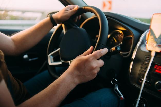 Homem está dirigindo as mãos do carro no volante