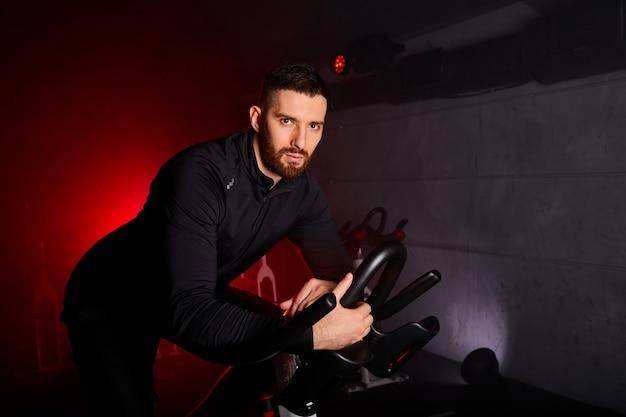 Homem está envolvido em uma bicicleta ergométrica, treinamento pessoal na academia iluminada por néon vermelho, vestindo um agasalho esportivo