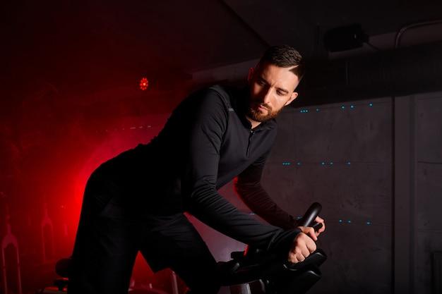 Homem está envolvido em uma bicicleta ergométrica, treinamento pessoal na academia iluminada por néon vermelho, vestindo um agasalho
