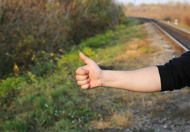 Homem está esperando o trem nos trilhos ao ar livre. conceito de viagens. ideias de verão. transporte atrasado. segurando o polegar com um sinal semelhante.