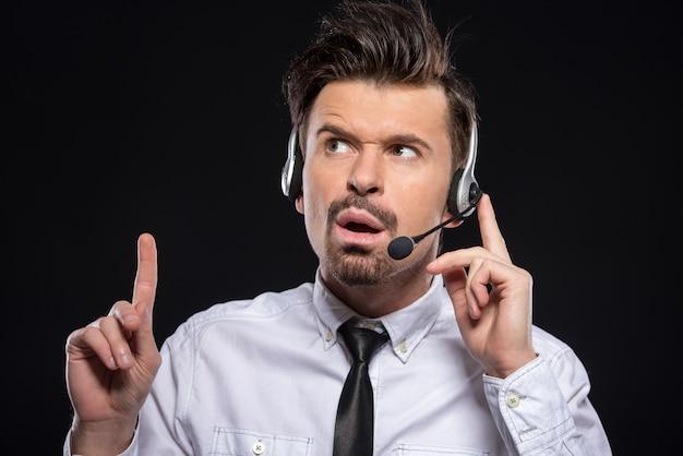 Homem está falando com fones de ouvido e microfone.