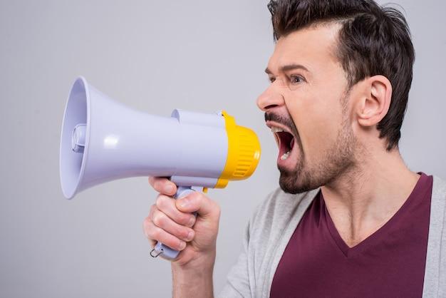 Homem está fazendo anúncio sobre um megafone.