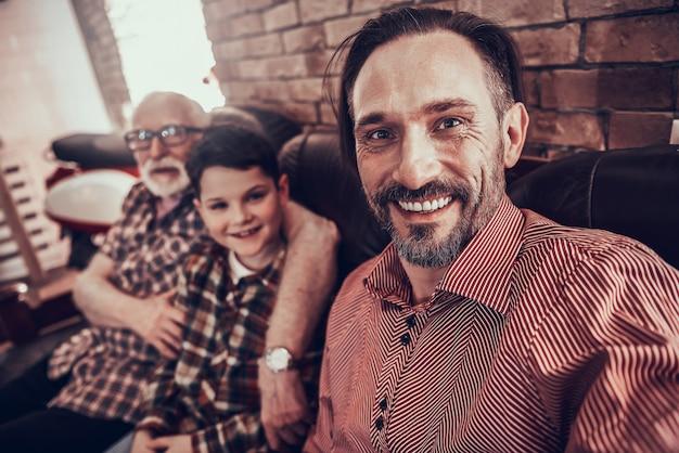 Homem está fazendo selfie com a família na barbearia.