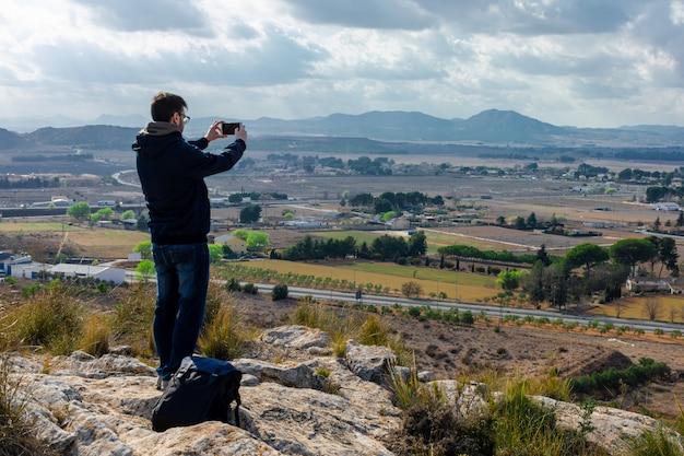 Homem está gravando vídeo do belo pôr do sol no telefone celular