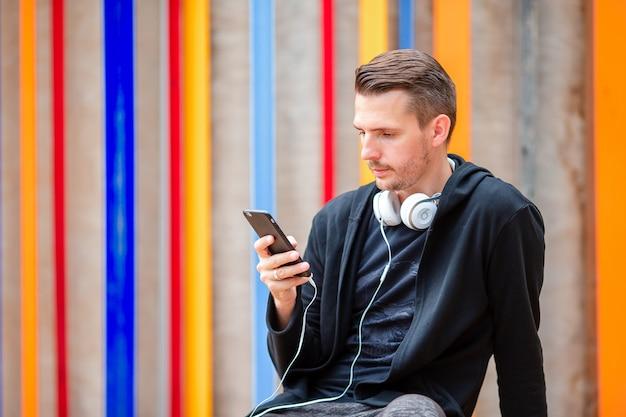 Homem está lendo a mensagem de texto no celular enquanto caminhava no parque