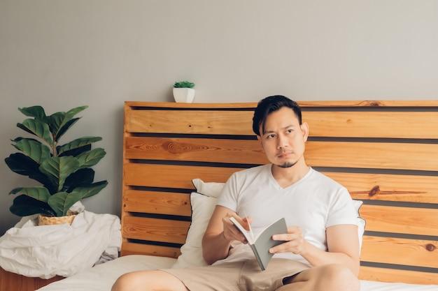 Homem está lendo um livro em sua cama no final da tarde.