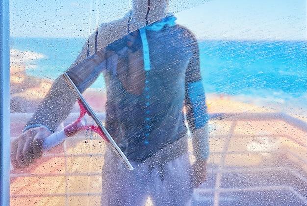 Homem está limpando a janela de vidro sujo com escova de limpador dentro vista