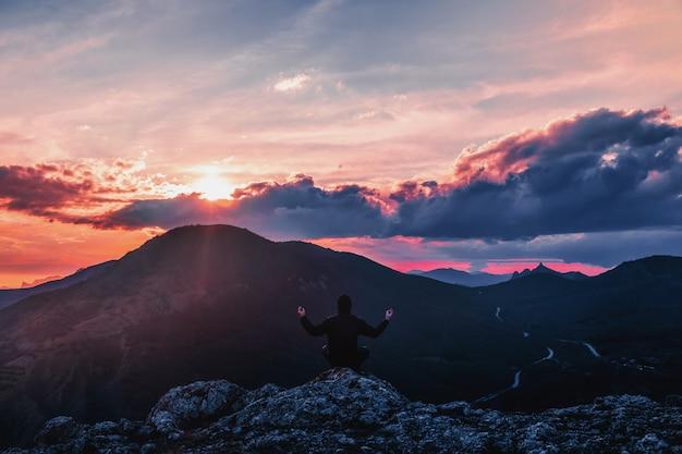 Homem está meditando nas montanhas ao pôr do sol.