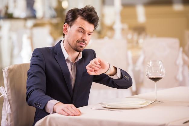 Homem está olhando para o relógio enquanto está sentado no restaurante.