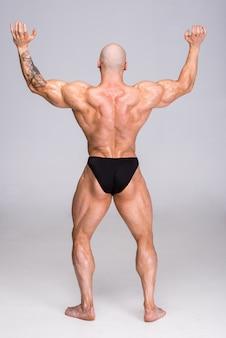 Homem está posando e mostra seus músculos.
