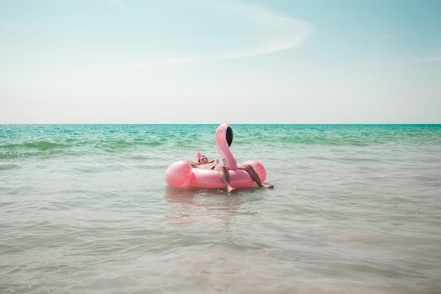 Homem está se divertindo no flutuador de piscina inflável flamingo rosa