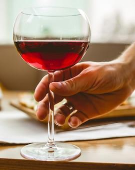 Homem está segurando o copo com vista lateral para vinho tinto