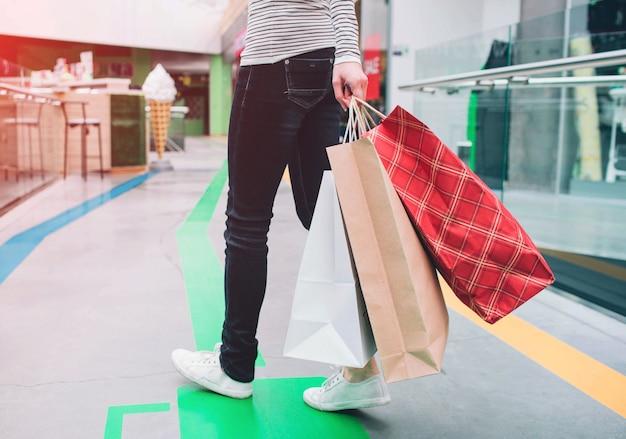 Homem está segurando sacolas de compras na mão esquerda
