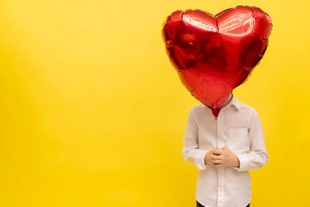 Homem está segurando um grande balão em forma de coração. saudações de feliz dia dos namorados.
