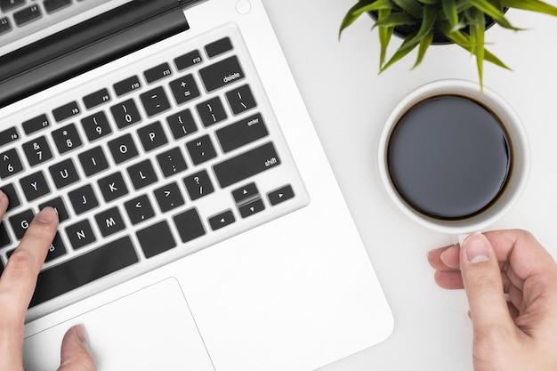 Homem está segurando uma xícara de café enquanto trabalhava usando o laptop.