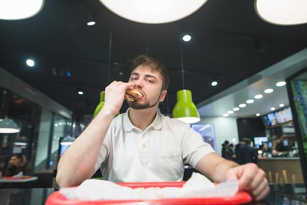Homem está sentado à mesa em um café e come um sanduíche delicioso. lanche no restaurante de fast food.