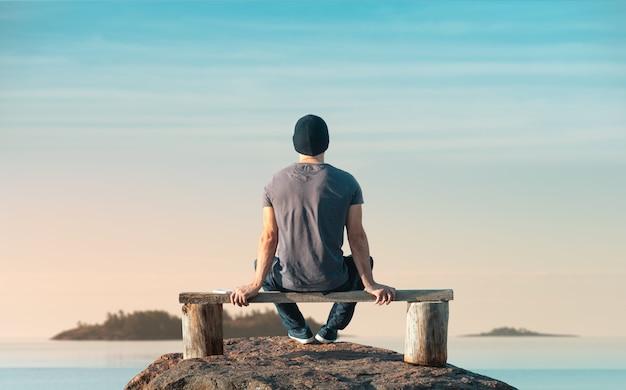 Homem está sentado em um banco de madeira. ele olha para o mar. vista traseira