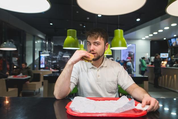 Homem está sentado em uma mesa em um restaurante rápido, comendo comida deliciosa