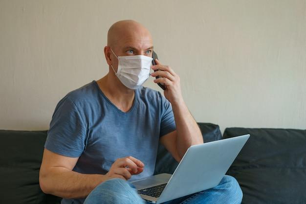 Homem está sentado no sofá em máscara protetora com um laptop e telefone, trabalho remoto em quarentena