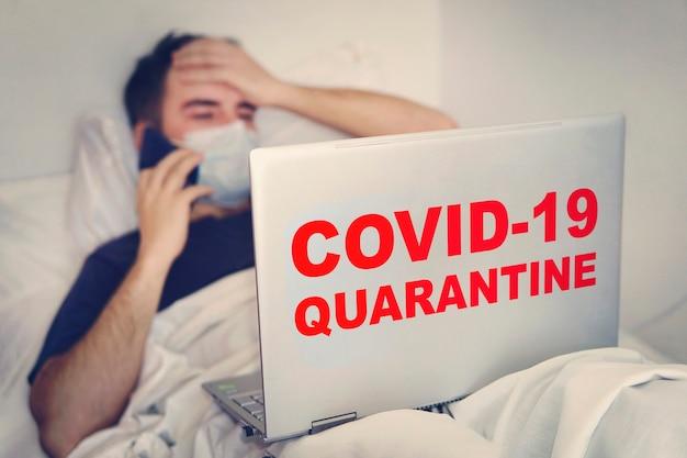 Homem está trabalhando em casa durante a quarentena de coronavirus ou covid-19, paciente infectado por coronavírus covid 19 na sala de quarentena de coronavírus usando computador. paciente liga ao telefone. conceito.