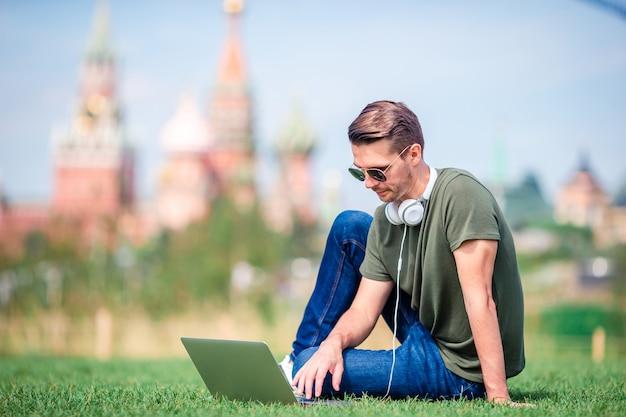 Homem está trabalhando pelo laptop enquanto relaxa no parque