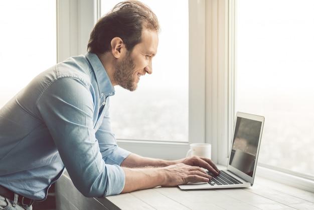 Homem está trabalhando perto da janela no escritório