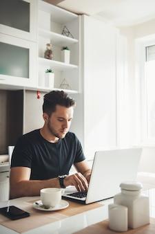 Homem está trabalhando remotamente de casa usando um laptop