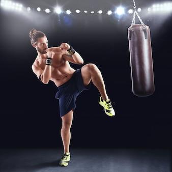 Homem está treinando com o saco de pancadas na academia