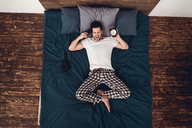 Homem está vestindo calça de pijama e t-shirt.